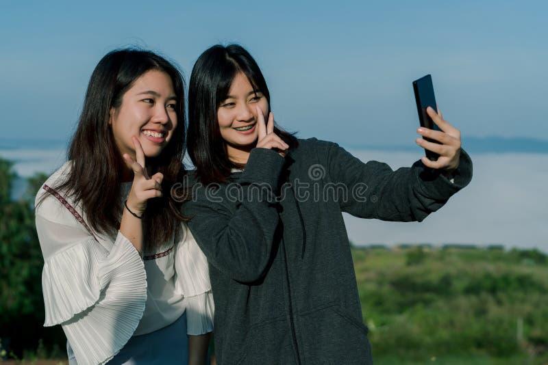 穿毛线衣的两个亚裔女孩,在旅游区采取selfie电话,在雾和山后拍照片与a 免版税库存图片