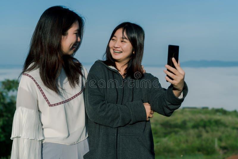 穿毛线衣的两个亚裔女孩,在旅游区采取selfie电话,在雾和山后拍照片与a 库存图片
