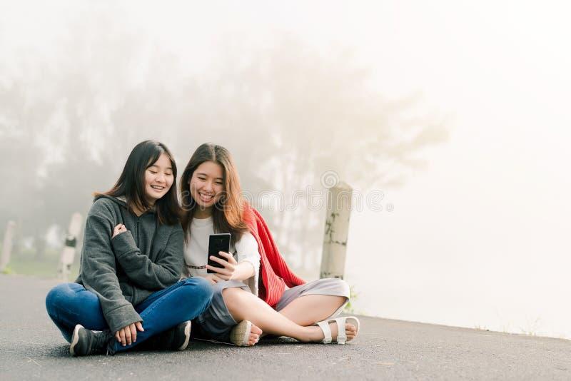 穿毛线衣的两亚裔女孩亲密朋友,采取一个selfie电话,沿在水库旁边的路在大雾Wi 图库摄影