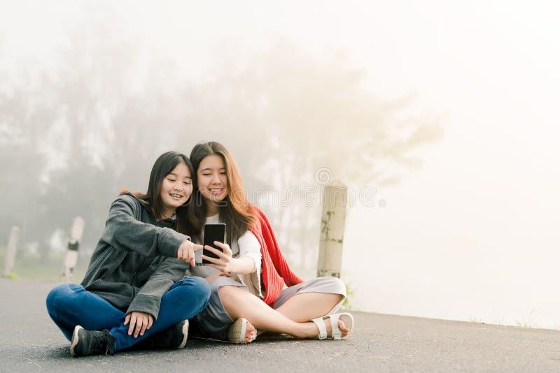穿毛线衣的两亚裔女孩亲密朋友,采取selfie电话,拍在一旅游景点的照片沿路 免版税图库摄影
