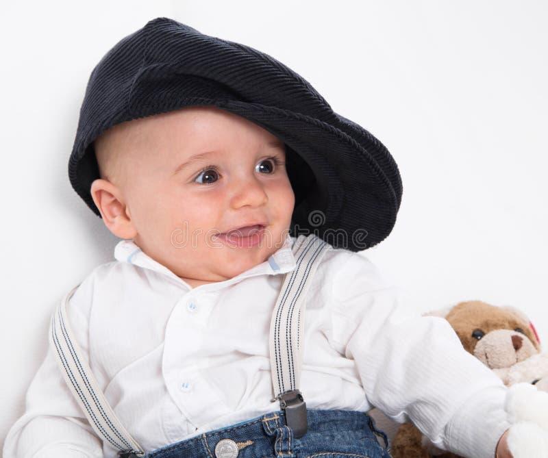 穿法国贝雷帽的笑的婴孩和蓝色牛仔裤 免版税库存照片