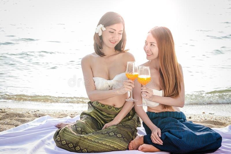 穿泰国礼服的美女,坐海滩 免版税库存照片