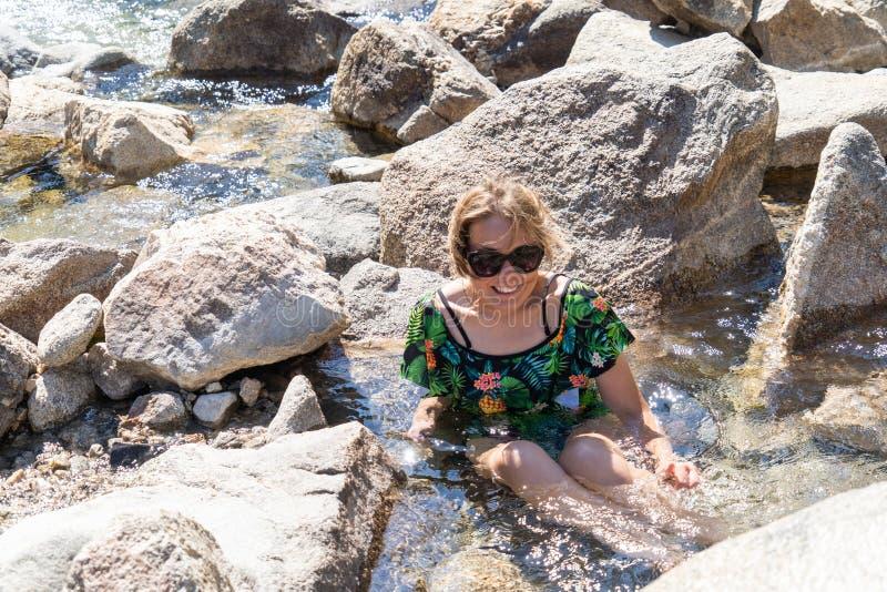 穿泳装的愉快的妇女坐在Sacajawea温泉城在爱达荷,在河附近的自然温泉城 免版税库存照片