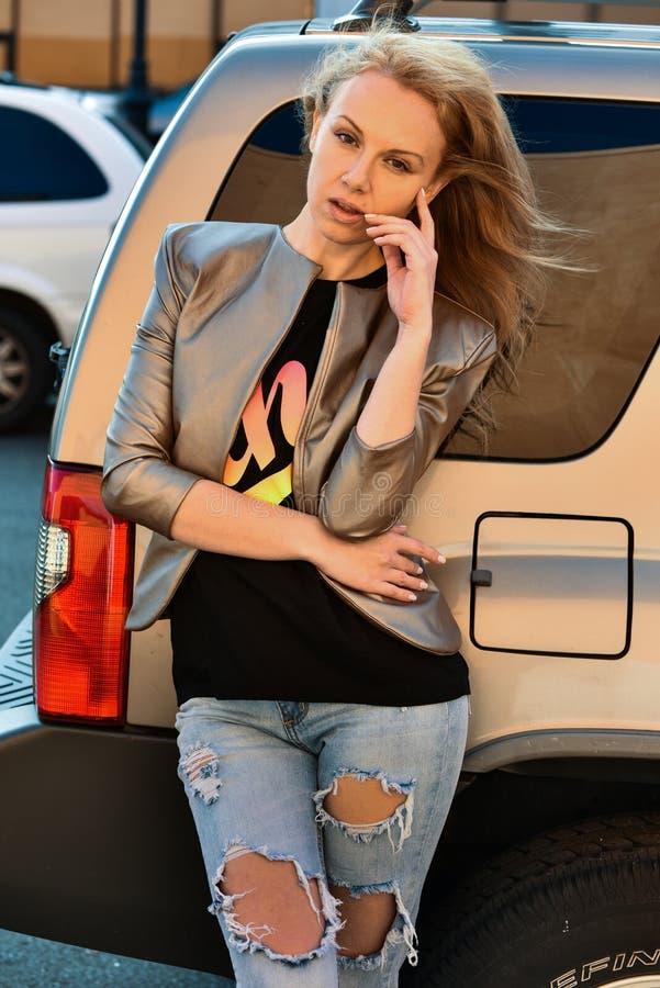 穿流行的服装的美丽的白肤金发的少妇,摆在汽车 免版税库存照片
