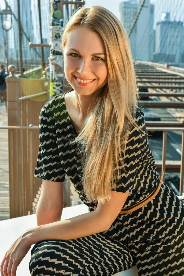 穿流行的服装的美丽的白肤金发的少妇画象,微笑看照相机 库存照片