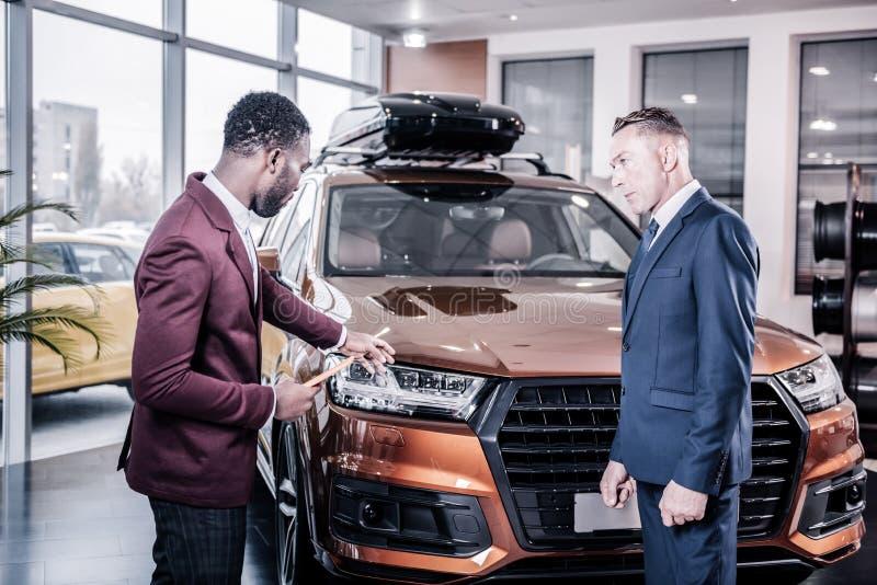穿深红夹克的专业汽车顾问协助客户 免版税库存照片