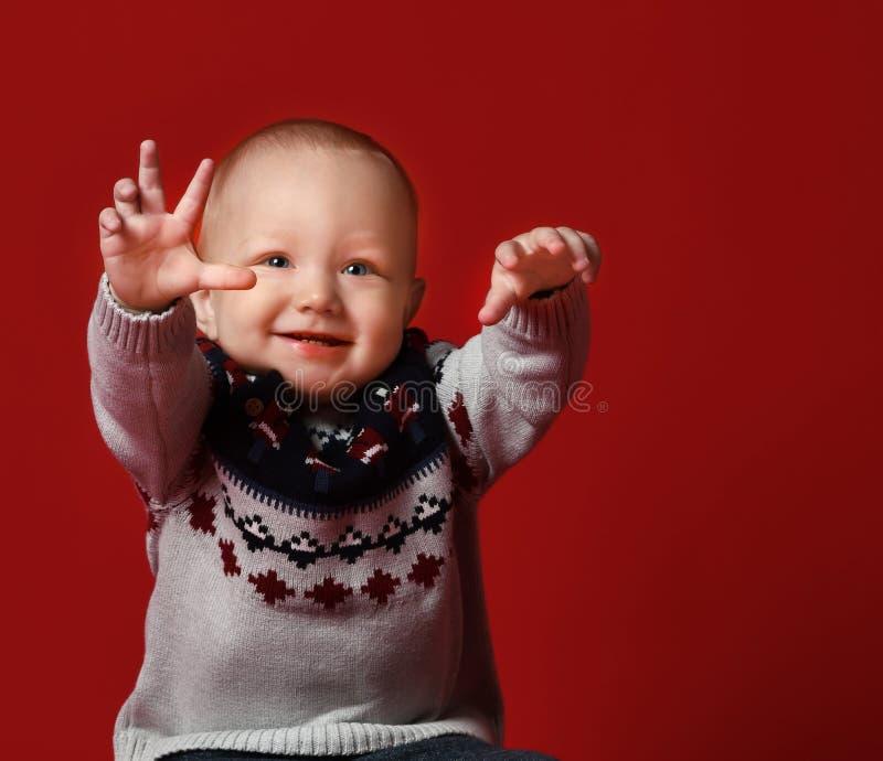 穿温暖的被编织的圣诞节毛线衣的滑稽的矮小的婴孩在演播室在寒冷冬天天 免版税图库摄影