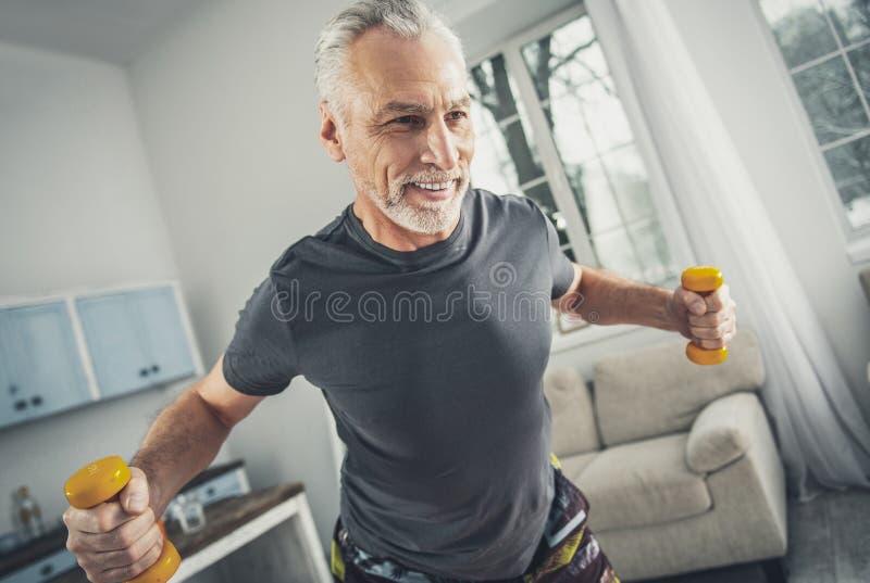 穿灰色衬衣的微笑的运动员举行哑铃 免版税库存照片