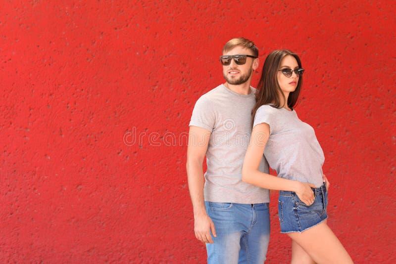 穿灰色T恤杉的年轻夫妇临近颜色墙壁 库存照片