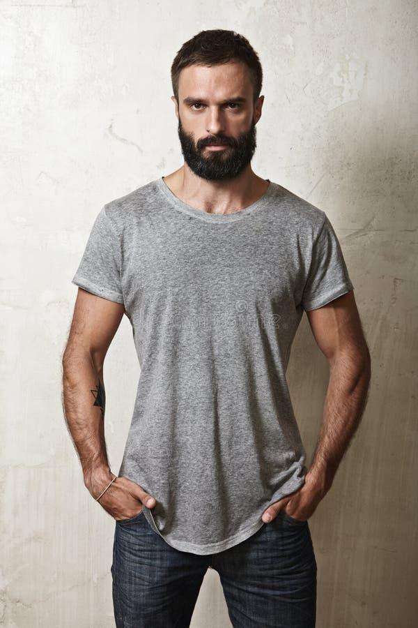穿灰色T恤杉的有胡子的人 库存照片