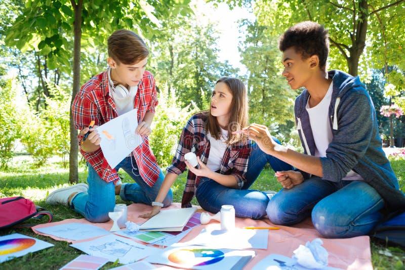 穿牛仔裤的三名时髦的学生做他们的家庭任务 免版税库存照片