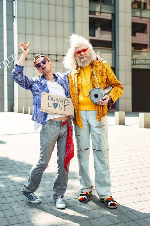 穿牛仔裤的两个微笑的花孩子大声唱歌  免版税库存图片