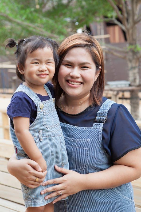 穿牛仔裤的母亲和孩子适合微笑的面孔激动幸福 库存照片