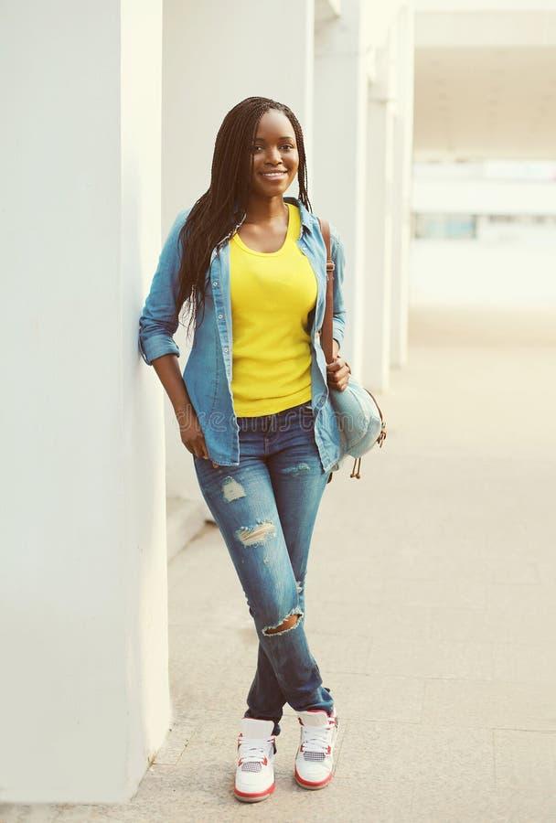 穿牛仔裤衬衣的美丽的愉快的微笑的非洲妇女 库存图片