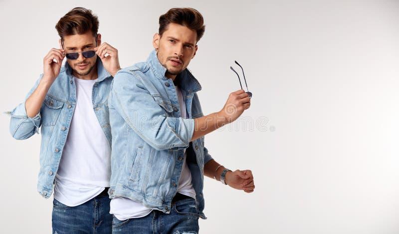 穿牛仔裤`夹克的一个年轻时髦的人的特写镜头画象 库存图片