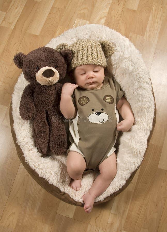 穿玩具熊帽子和连裤外衣的男婴 免版税图库摄影