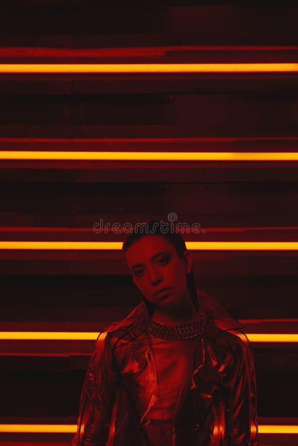 穿玻璃纸和红色礼服的透明外套模型计算机国际庞克射击对氖墙壁  图库摄影