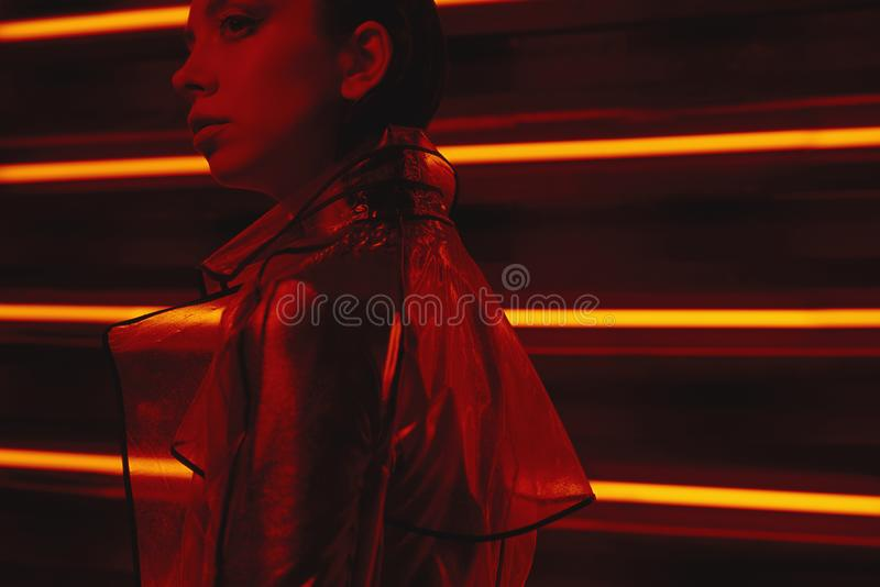 穿玻璃纸和红色礼服的透明外套模型计算机国际庞克射击对氖墙壁  免版税图库摄影