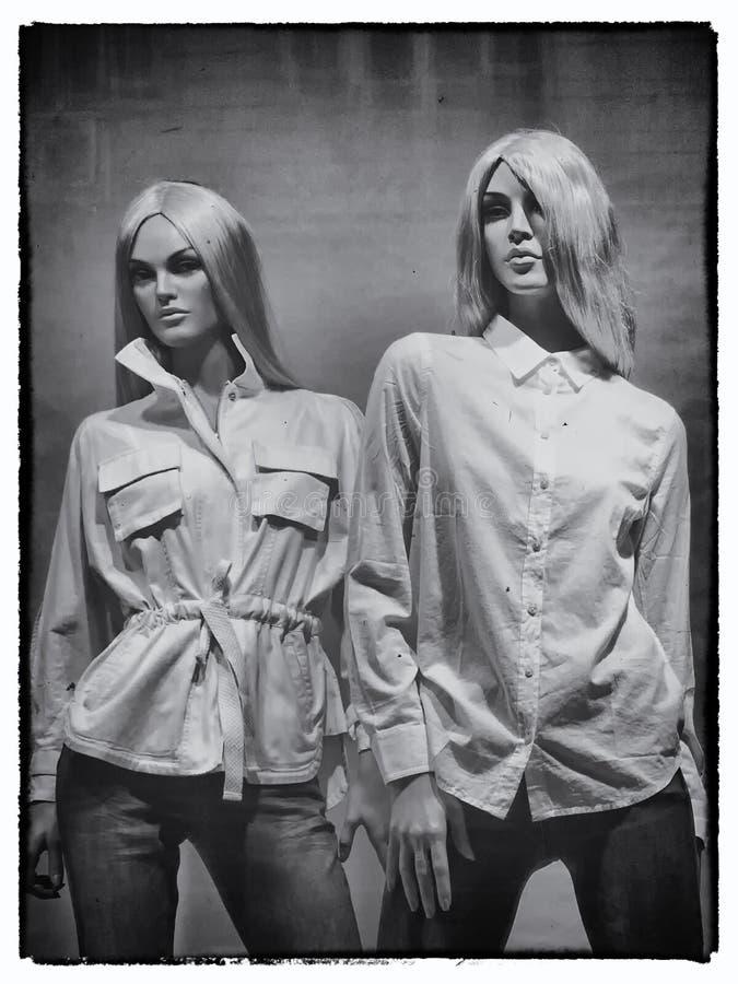 穿白色衬衣和牛仔裤的两个幼小白肤金发的母时装模特 免版税库存照片