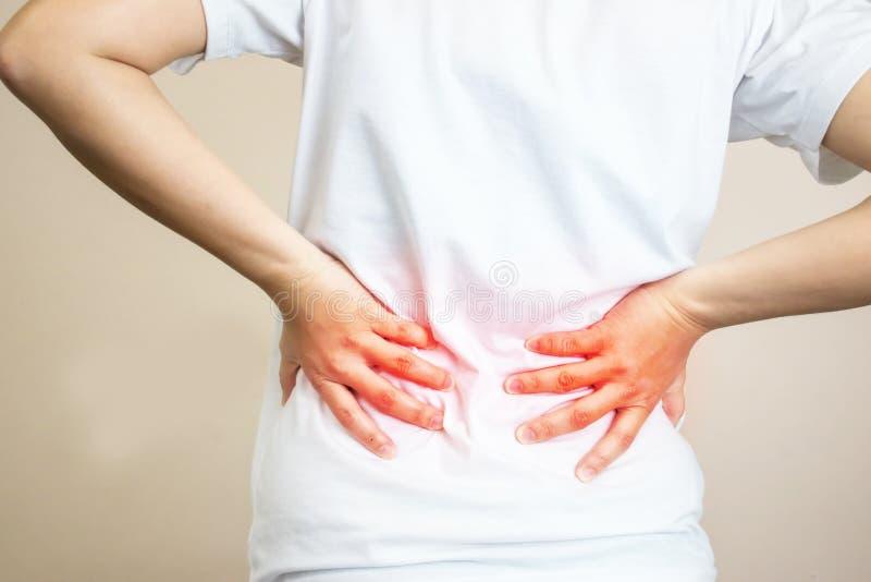 穿白色衬衫的妇女感觉背部疼痛 我在许多小时工作 免版税图库摄影