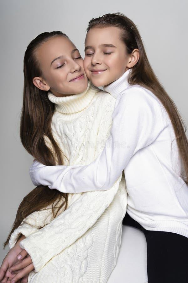 穿白色高领衫毛线衣的两位逗人喜爱的少年女朋友女小学生,微笑坐,拥抱用一个友好的方式 免版税库存图片