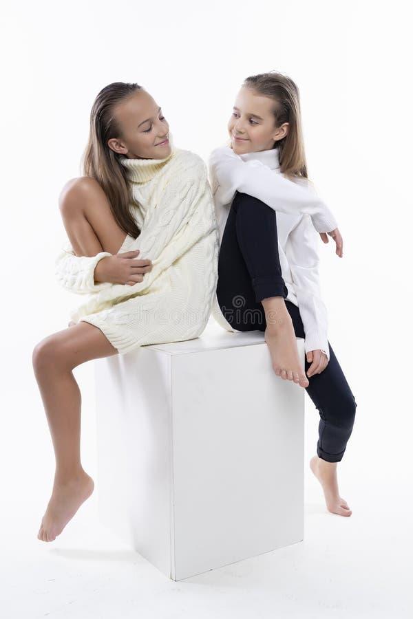 穿白色高领衫毛线衣的两位逗人喜爱的少年女朋友女小学生,微笑紧接坐 在白色 方式 免版税库存照片