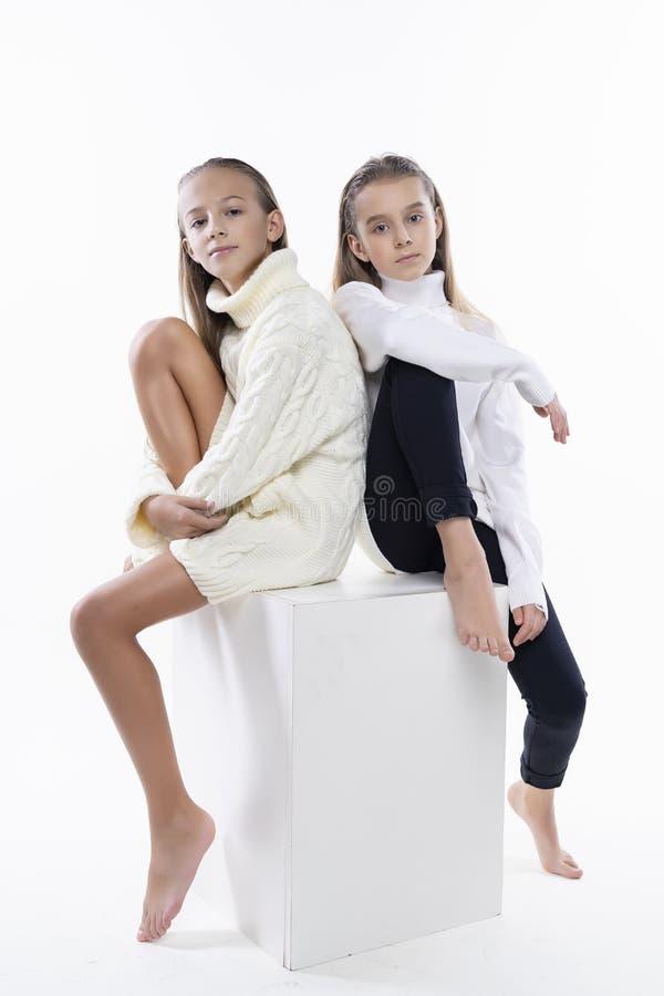 穿白色高领衫毛线衣的两位逗人喜爱的少年女朋友女小学生,微笑紧接坐 在白色 时尚a 图库摄影