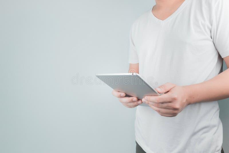 穿白色T恤的英俊的年轻亚洲人站立拿着一种数字片剂 生活方式 库存照片