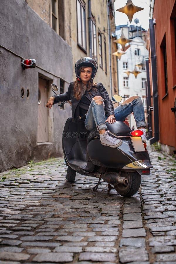 穿皮夹克和被剥去的牛仔裤的美女坐在老狭窄的街道上的一辆黑经典滑行车  免版税库存图片
