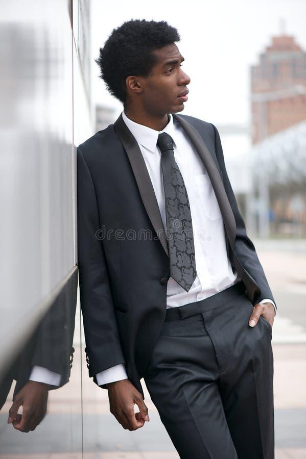 穿着一套西装的一个英俊的年轻黑人的画象在城市 库存图片