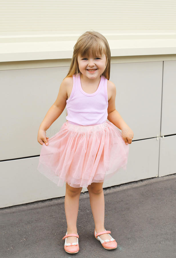 穿着一条桃红色裙子的小女孩孩子户外 图库摄影