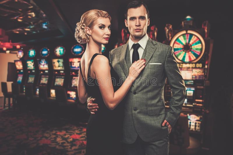 穿着体面的减速火箭的样式夫妇在赌博娱乐场 免版税库存照片