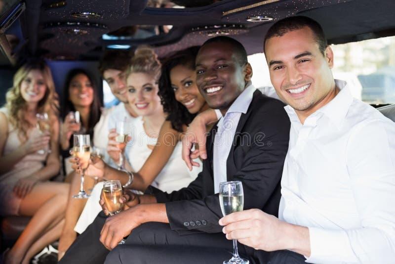 穿着体面的在大型高级轿车的人民饮用的香槟 免版税库存图片