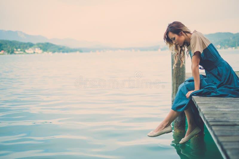 穿着体面的妇女坐木码头有山河视图 图库摄影
