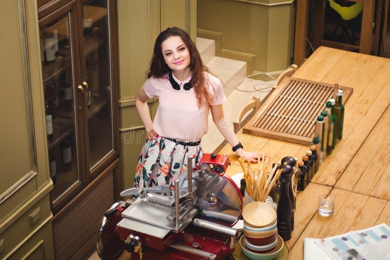 穿着体面的年轻美丽的女孩在意大利s的厨房里站立 库存照片