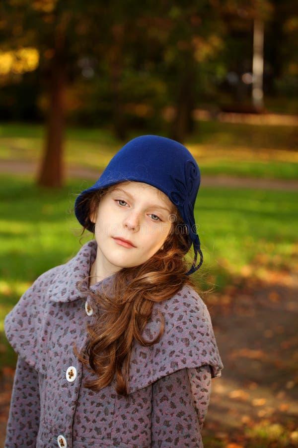 穿着减速火箭的呢帽的女孩。 室外 库存照片