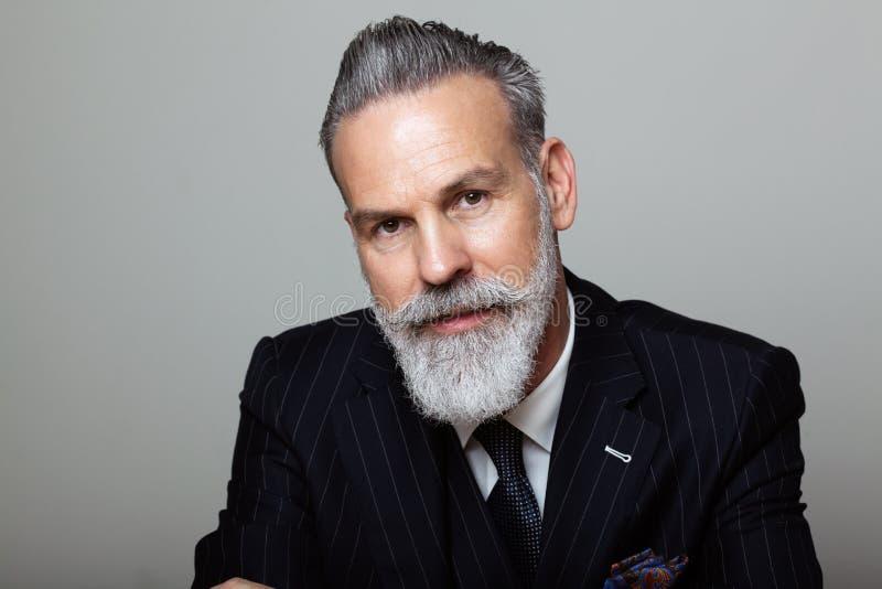 穿着在空的灰色背景的可爱的有胡子的绅士画象时髦衣服 演播室射击,时尚概念 免版税库存图片