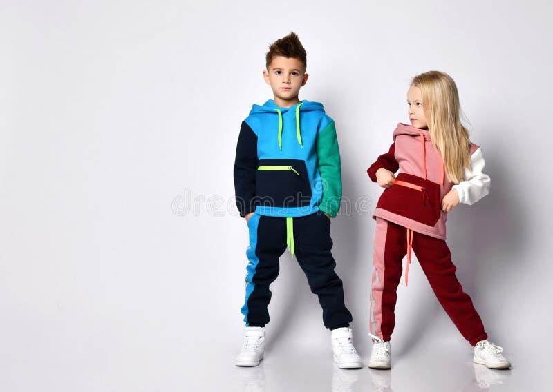 穿着彩色运动服和运动鞋的小孩,男孩和女孩 他们在白色工作室背景中独立摆姿势 手放在口袋里 免版税库存图片