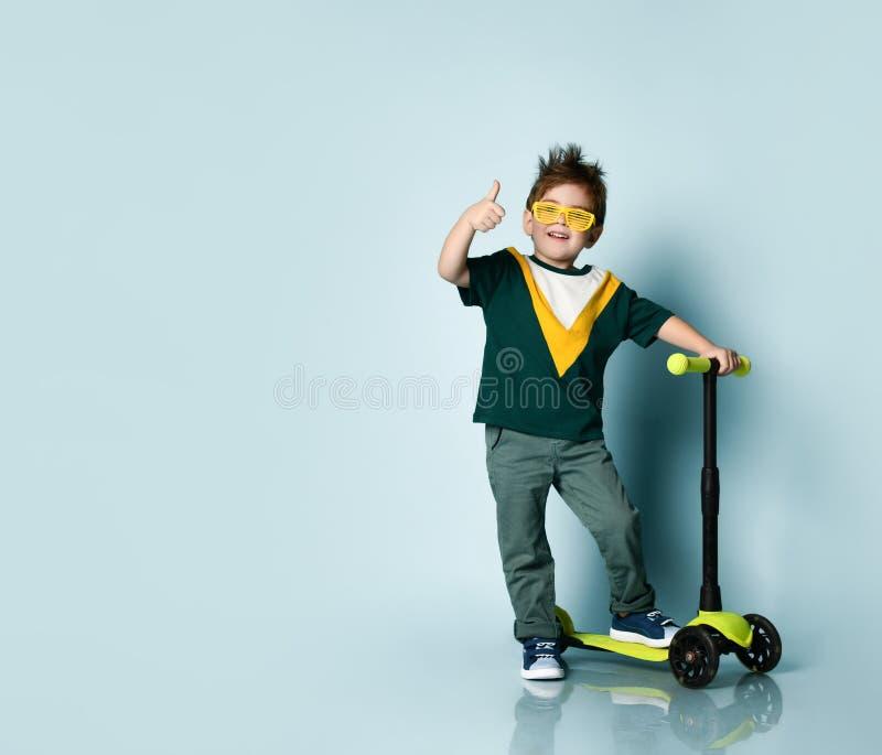 穿着彩色T恤,黄色太阳镜,牛仔裤,运动鞋的男孩 手举起尖叫,站在踏板车上 蓝色背景 免版税库存图片