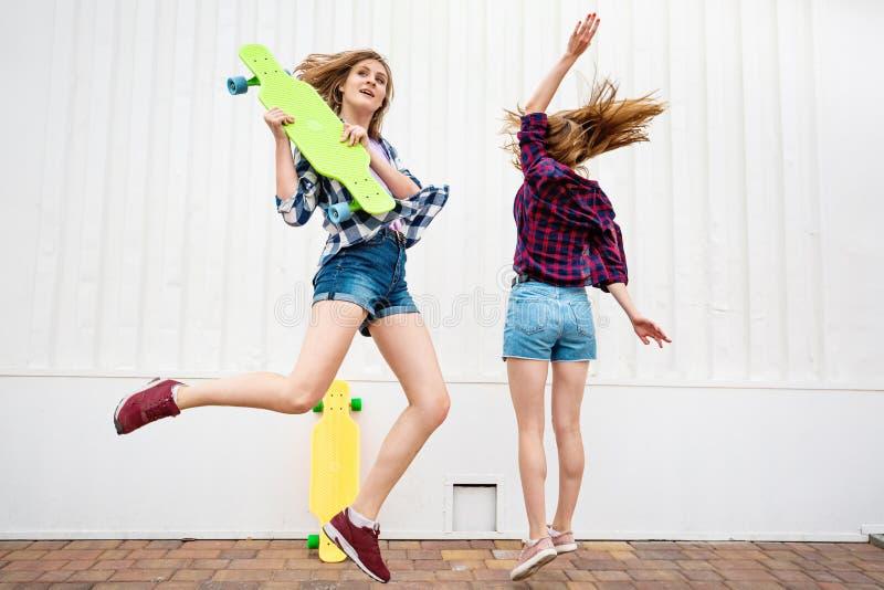 穿着方格的衬衣和牛仔布短裤的两个相当白肤金发的女孩是跳和跳舞与明亮的longboards 年轻 库存图片