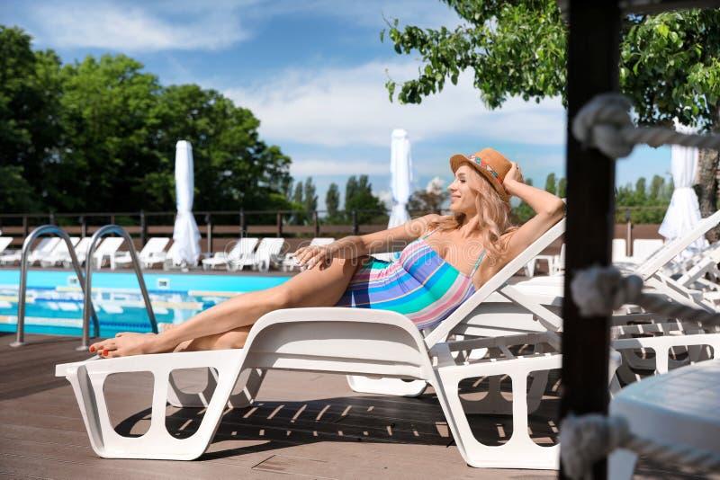 穿着时尚比基尼的性感年轻女性,在游泳池附近的日光浴床上放松 免版税库存图片
