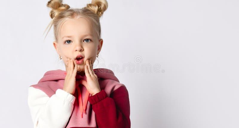 穿着时尚运动服、带时尚发型、口袋中手指的漂亮微笑女孩 库存照片