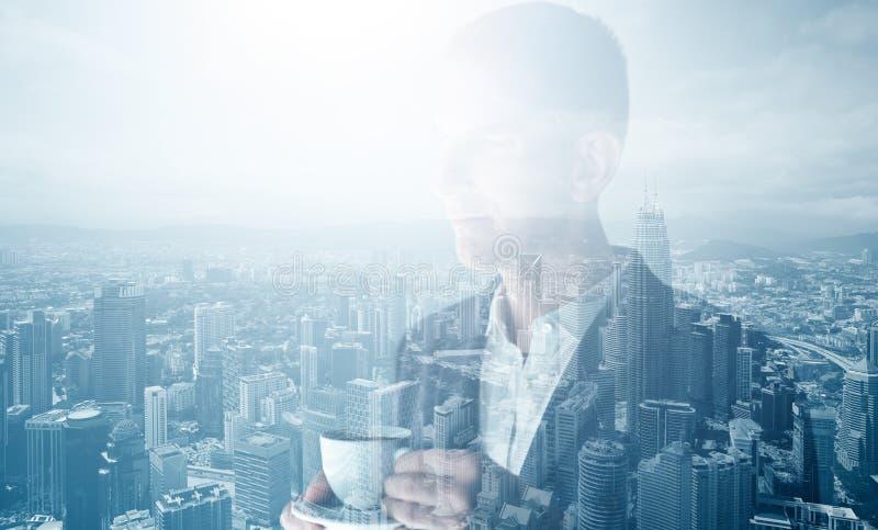 穿着时髦衣服和拿着杯子咖啡的时髦的成人商人照片  两次曝光,全景当代城市 免版税图库摄影