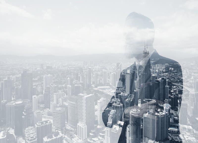 穿着时髦衣服的时髦的成人商人照片  两次曝光,全景当代城市背景 水平 免版税图库摄影