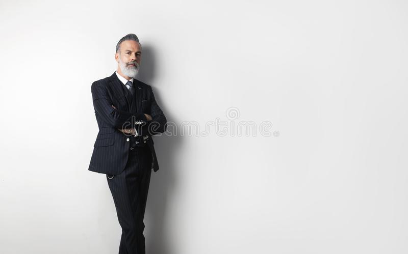 穿着时髦衣服的有胡子的确信的绅士画象站立在空的白色背景 复制浆糊文本空间 库存图片