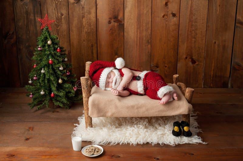 穿着有胡子的睡觉的新出生的男婴圣诞老人衣服 免版税库存照片