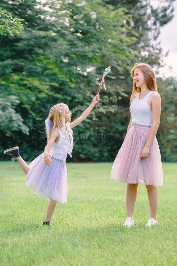 穿着桃红色芭蕾舞短裙薄纱裙子的两个微笑的滑稽的白种人女孩姐妹在公园森林草甸在日落 有朋友的乐趣 免版税库存图片
