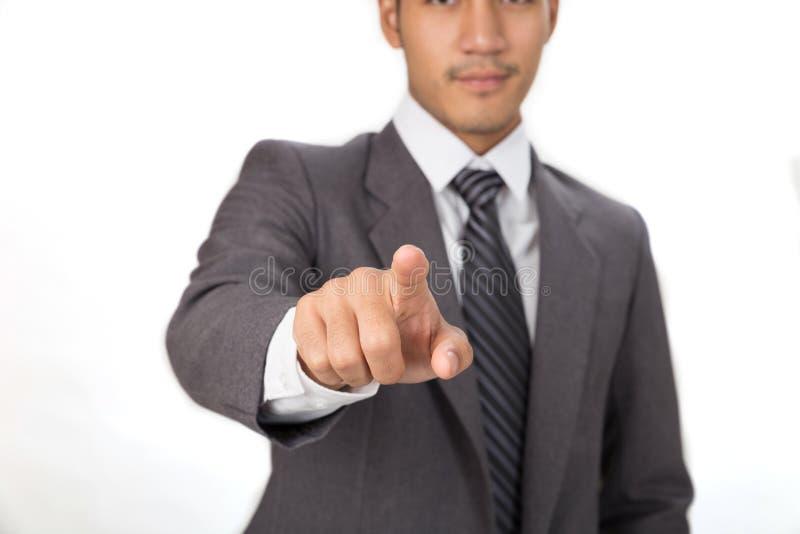 穿着灰色衣服的商人站立和指向照相机ov 库存图片