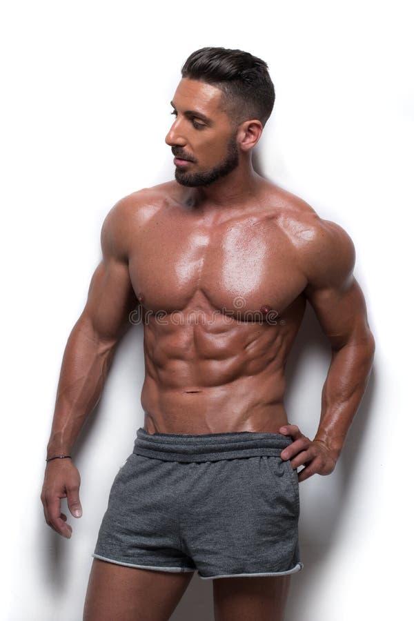 穿着灰色运动短裤的肌肉人 库存图片