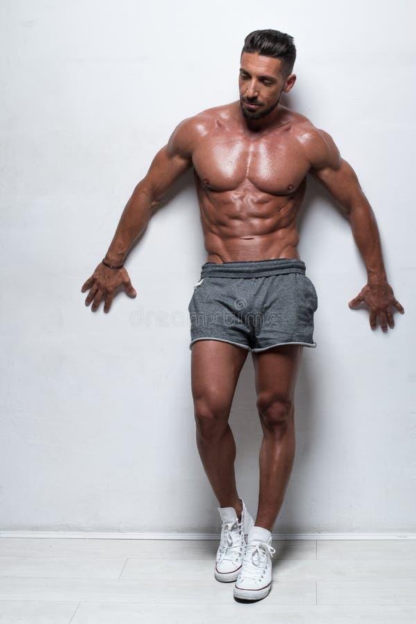 穿着灰色运动短裤的肌肉人 免版税库存照片